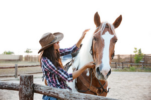 Closeup of beautiful young woman cowgirl with horse in village
