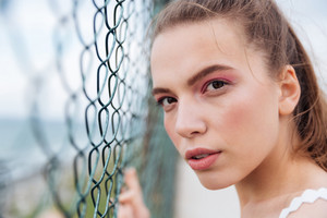 Closeup of beautiful young woman standing near chain link fence