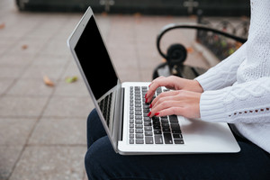 Closeup of blank screen laptop used by young woman hands sitting on bench outdoors
