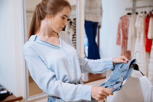 Closeup of cute young woman thinking and choosing clothes in clothing shop