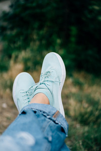 Closeup of female legs in jeans and sneakers on a background of trees. Shallow depth of field, copy space.