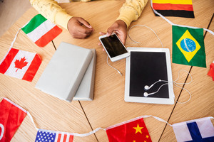 Closeup of hands of man using cell phone at the table with tablet, books and flags of countries