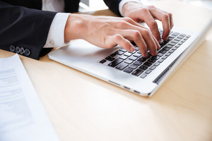Closeup of hands of young businessman using laptop at the table