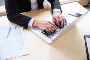 Closeup of hands of young businessman working using laptop in office