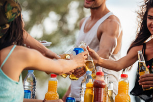 Closeup of hands of young friends celebrating and drinking beer outdoors