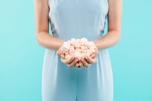 Closeup of hands of young woman holding marshmallows over blue background