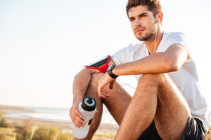 Closeup of handsome young sportsman sitting and holding bottle of water outdoors