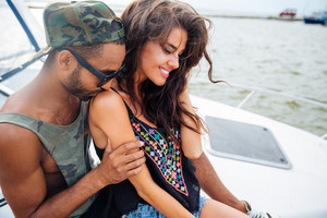 Closeup of happy sensual young couple kissing and embracing on boat