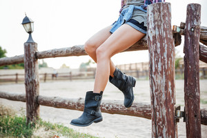 Closeup of legs of young woman cowgirl in shorts and boots sitting on fence