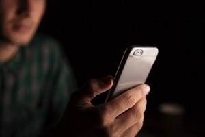 Closeup of man hand sitting and using smartphone in the evening