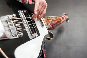 Closeup of man hands holding and playing guitar over grey background