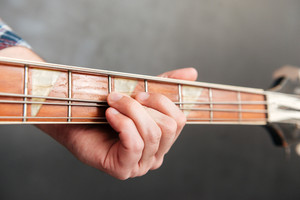Closeup of man hands playing guitar over grey background