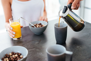 Closeup of man pouring coffee into the cup and having breakfast with his girlfriend on the kitchen