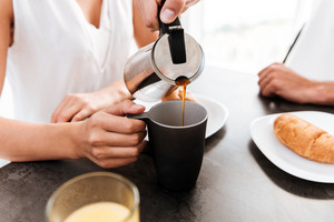 Closeup of man pouring coffee into the cup of his girlfriend on the kitchen