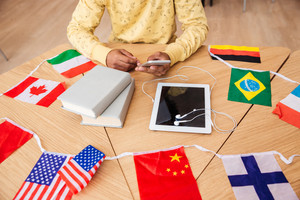 Closeup of man sitting at the table with tablet, books and flags of countries