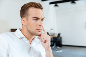 Closeup of pensive young businessman sitting and thinking in office