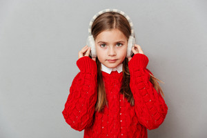 Closeup of pretty little girl in red sweater and earmuffs