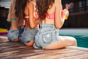 Closeup of seductive young women in jeans shorts sitting near swimming pool