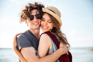 Closeup of sensual young couple with backpacks standing and hugging in the beach