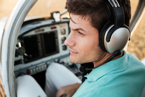 Closeup of serious handsome young man pilot with headset in cabin of plane
