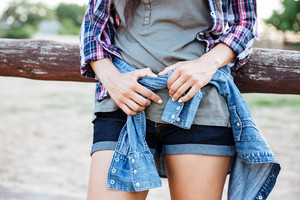 Closeup of slim young woman in jeans shorts standing outdoors