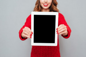 Closeup of smiling young woman in santa claus hat showing blank screen tablet over gray background