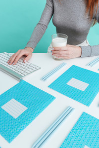 Closeup of woman drinking milk and working with computer over blue background