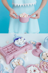 Closeup of woman holding plastic pot with marshmallows and playing over blue background