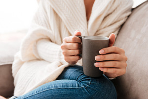 Closeup of woman sitting and holding cup of coffee on couch at home