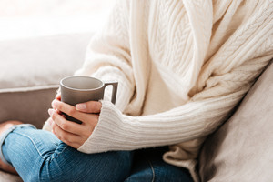 Closeup of woman with cup of coffee sitting on sofa at home