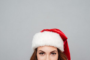 Closeup of young woman in red santa claus hat over gray background