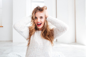 Closeup portrait of a cheerful woman touching her hair indoors