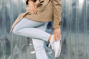 Clothing details: girl in a beige coat, jeans and sneakers outdoors