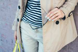 Clothing Details: woman in beige coat holding sun glasses and handbag close-up