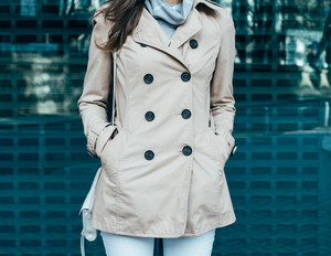 Clothing details: woman in jeans and a beige coat outdoors, close-up