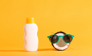 Coconut wearing sunglasses and sunscreen on a bright yellow background