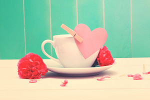 Coffee cup with a pink heart tag and carnations on a teal colored wood background