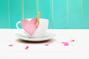Coffee cup with heart tag and flower petals over blue green wooden wall