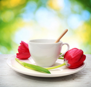Coffee cup with red tulips in shiny leaves background