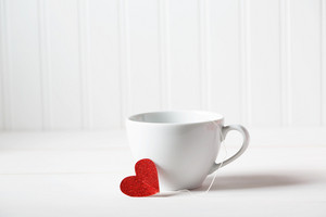 Coffee cup with small heart on white wooden background