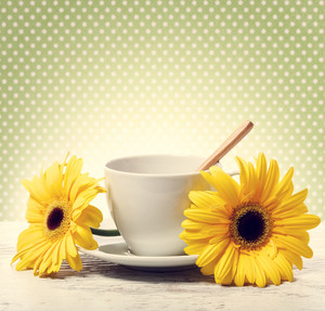 Coffee cup with yellow gerberas over green polka dot background