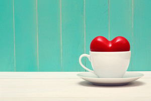 Coffee filled with love on vintage style teal wood background
