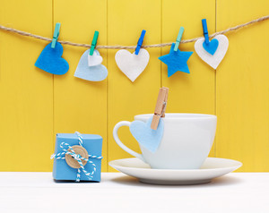 Coffee for a loved one or sweetheart decorated with pretty blue and white hearts hanging from clothes pegs over a yellow background of rustic wooden boards with a small gift box