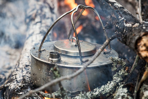 Coffee pot in camp fire. Making coffee outside.