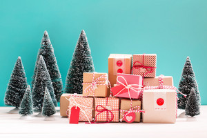 Collection of little handmade gift boxes in a snow covered miniature evergreen forest