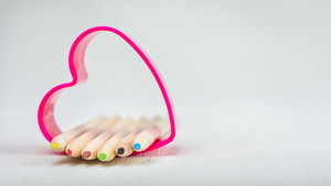 Color pencils laying in red heart symbol and represent love to creativity drawing
