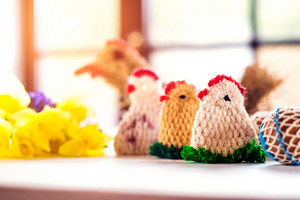 Colorful crocheted Easter chickens and fresh daffodil bouquet laid on white wooden table