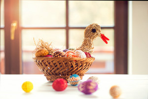 Colorful crocheted Easter eggs and straw hen in wicker basket