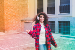 Colorful filtered young beautiful mixed race woman outdoor in the city dancing listening music with headphones - freedom, enjoying, music concept