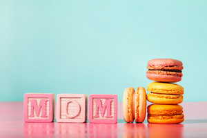 Colorful macarons with mom wood blocks for mothers day on bright pastel background